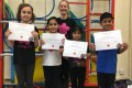 Big Buds proudly showing their Grade One and Grade Two certificates and button badges after achieving the grades in the Blossom Yoga Syllabus