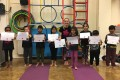Lil' Buds proudly showing their Grade One, Grade Two, Grade Three and Grade Four certificates and badges after achieving the grades in the Blossom Yoga Syllabus