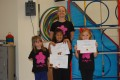 Lil' Buds proudly showing their Grade One and Two certificates and badges after achieving the grades in the Blossom Yoga syllabus