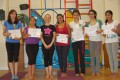 Teen Buds proudly showing their Grade Two and Four certificates and button badges after achieving the grades in the Blossom Yoga syllabus