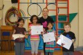 Lil' Buds proudly showing their Grade One, Two and Three certificates and badges after achieving the grades in the Blossom Yoga syllabus