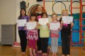 Big Buds proudly showing their Grade One, Two and Three certificates and button badges after achieving the grades in the Blossom Yoga syllabus