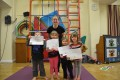 Lil' Buds proudly showing their Grade Two and Three certificates and badges after achieving the grades in the Blossom Yoga syllabus