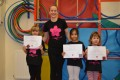 Lil' Buds proudly showing their Grade One certificates and badges after achieving the grade in the Blossom Yoga Syllabus