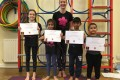 Lil' Buds proudly showing their Grade One and Grade Two badges and certificates after achieving the grades in the Blossom Yoga Syllabus
