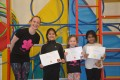 Lil' Buds proudly showing their Grade Two and Grade Three certificates and badges after achieving the grades in the Blossom Yoga Syllabus