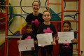 Lil' Buds proudly showing their Grade One and Grade Three certificates and badges after achieving the grades in the Blossom Yoga Syllabus