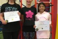 Teen Buds proudly showing their Grade Three and Grade Four certificates and button badges after achieving the grades in the Blossom Yoga Syllabus