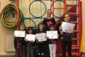 Lil' Buds proudly showing their Grade Four and Grade Five certificates and badges after achieving the grades in the Blossom Yoga Syllabus
